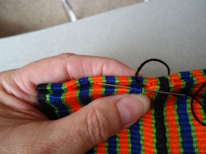 Attaching tab to pouch at the top of the back of the band, weaving a fresh weft through an old shed
